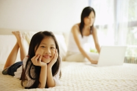 Mother and daughter in bedroom, mother using laptop, daughter looking at camera - Alex Microstock02