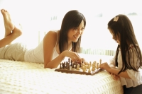 Mother and daughter playing chess in bedroom - Alex Microstock02