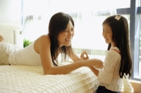 Mother and daughter in bedroom, mother tickling daughter - Alex Microstock02