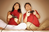 Man and woman sitting side by side, legs crossed, playing with handheld video game - Alex Microstock02