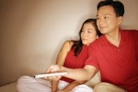 Man and woman sitting side by side, man with remote control - Alex Microstock02