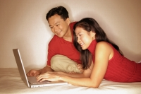 Man and woman side by side, using laptop - Alex Microstock02
