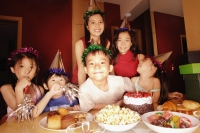 Young boy at a birthday party, surrounded by friends - Alex Microstock02