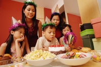 Young boy blowing out candles on a cake, surrounded by friends - Alex Microstock02