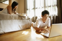 Young man using laptop, young woman lying on bed reading magazine - Alex Microstock02