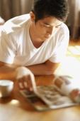 Young man reading magazine - Alex Microstock02