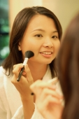 Woman putting on make-up with a blush brush - Alex Microstock02