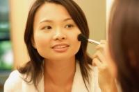 Woman putting on make-up with a blush brush - Alex Microstock02