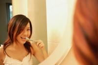 Woman brushing her teeth, looking at mirror - Alex Microstock02