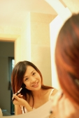 Woman putting on mascara, looking at mirror, smiling - Alex Microstock02