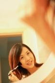 Woman putting on mascara, looking at mirror, smiling - Alex Microstock02
