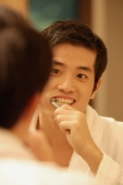 Young man brushing his teeth, looking in mirror - Alex Microstock02
