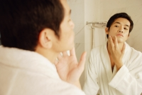 Young man touching his face, looking in mirror - Alex Microstock02