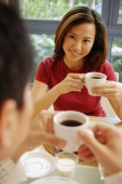 Couple facing each other, holding cups of coffee - Alex Microstock02