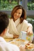 Couple having breakfast, woman pouring milk. - Alex Microstock02