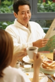 Couple at breakfast table, man holding newspaper - Alex Microstock02