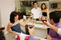 Group of friends having a dinner party at home, some raising wine glass - Alex Microstock02