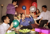 Group of friends having a party at home, holding balloons - Alex Microstock02
