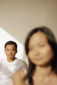 Young man looking at camera, woman in front of him - Alex Microstock02