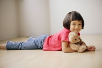 Young girl lying on front, hugging teddy bear. - Alex Mares-Manton
