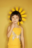 Young girl standing against yellow background, hand on chin - Alex Microstock02