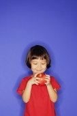 Young girl standing against blue background, holding an apple - Alex Microstock02