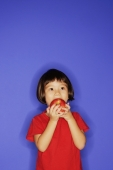 Young girl standing against blue background, biting an apple - Alex Microstock02