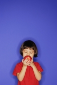 Young girl standing against blue background, holding an apple and biting it. - Alex Microstock02