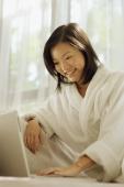 Young woman wearing robe, using laptop - Alex Microstock02