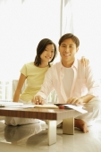Couple sitting side by side at home, documents and papers in front of them. - Alex Microstock02