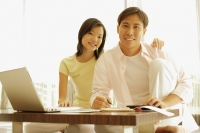 Couple sitting side by side at home, laptop open in front of them - Alex Microstock02