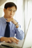 Male executive using laptop, hand on chin - Alex Microstock02
