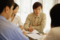 Young executives sitting face to face, having a meeting - Alex Microstock02