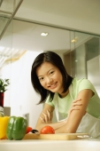 Young woman leaning on kitchen counter, arms crossed - Alex Microstock02