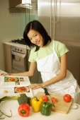 Young woman in kitchen with cookbook, looking at camera - Alex Microstock02
