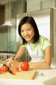 Young woman leaning on kitchen counter, hands clasped, looking at camera - Alex Microstock02