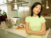 Young woman leaning on kitchen counter, looking at camera - Alex Microstock02