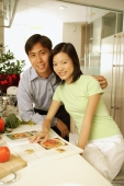 Couple in kitchen, side by side, looking at camera - Alex Microstock02