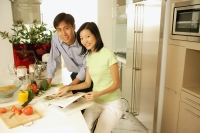 Couple in kitchen with cookbook, looking at camera - Alex Microstock02