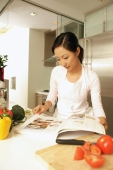 Young woman standing at kitchen counter, looking at cookbook - Alex Microstock02