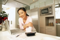 Young woman in kitchen, with laptop and calculator, looking at camera - Alex Microstock02