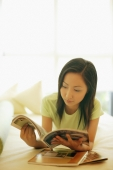 Young woman lying on bed, reading magazine - Alex Microstock02
