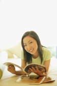 Young woman lying on bed, holding magazine, looking at camera - Alex Microstock02