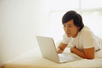 Young man lying on bed, using laptop - Alex Microstock02