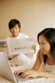 Couple in bedroom, man reading newspaper, woman using laptop - Alex Microstock02