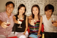 Couples sitting down raising wine glasses, looking at camera - Alex Microstock02