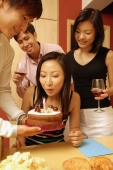 Woman blowing out candle on cake, surrounded by friends - Alex Microstock02
