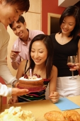 Woman looking at cake, surrounded by friends - Alex Microstock02