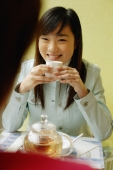 Young woman drinking tea, facing another person - Alex Microstock02