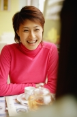Young woman sitting opposite another person, smiling, arms crossed - Alex Microstock02